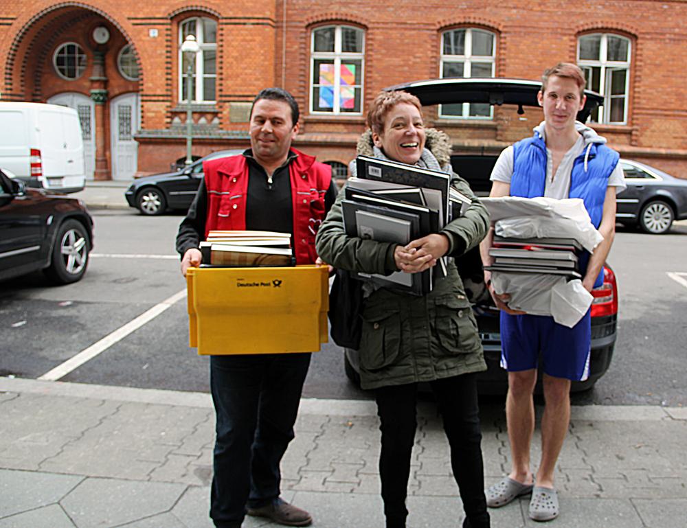 Heike Salchli (mitte) von Revolver Publishing bringt Bücher für eine kleine Bibliothek in die Notunterkunft Gotenburger Straße.