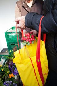 """Unumstritten ist diese Form der Lebensmittelrettung. Eine Kundin packt Radieschen bei der Lebensmittelausgabe des Sozialvereins """"Menschen helfen Menschen"""" in der Wollankstraße ein. Foto: Renter"""