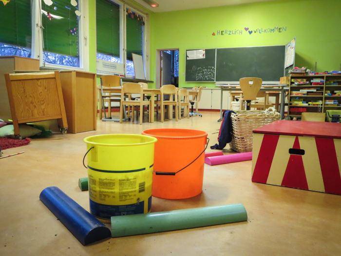 Eimer fangen im Klassenraum das Wasser von der Decke auf