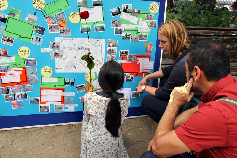 Ein Mädchen zeigt einer Politikerin an der Wandzeitung gute und weniger gute Orte im Stadtteil. Foto: Dominique Hensel