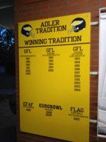 Ein gelbes Schild der Footballmannschaft Berlin Adler mit den gewonnenen Spielen aufgeschrieben.
