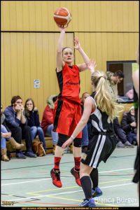 Basketballerin springt mit Ball zum Korbwurf. Basketball im Wedding
