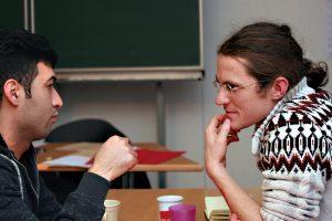 Ein Flüchtling und ein Pate unterhalten sich bei einem Kennenlerntreffen. Foto: Martin Reischke