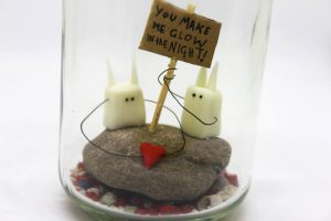 Eine Lampe aus einem Pastaglas mit kleinen Figuren.