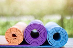 drei bunte Yogamatten zusammengerollt