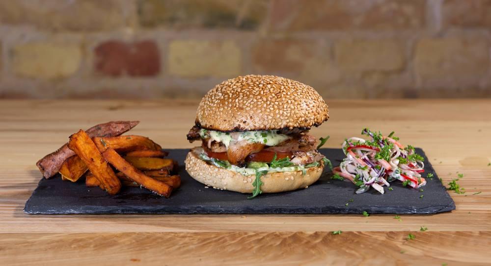Ein Burger mit Beilage auf einem Teller