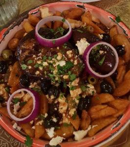 Ein Teller mit Pommes, Bratensauce, Käsestücken und Zwiebeln