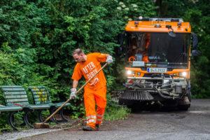 Mitarbeiter der Stadtreinigung reinigen eine Grünfläche. Foto: BSR
