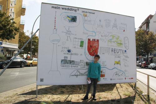 """Der jüngste Teilnehmer in diesem Jahr: Jakob Hensel vor dem Plakat mit seiner Zeichnung. Sei wird im Rahmen von """"Mein Wedding 5"""" auf der Müllerstraße gezeigt. Foto: D. Hensel"""
