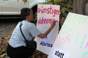 Eine Frau malt ein Plakat mit ihrem Nutzungswunsch für die ehemalige Schule. Foto: Hensel