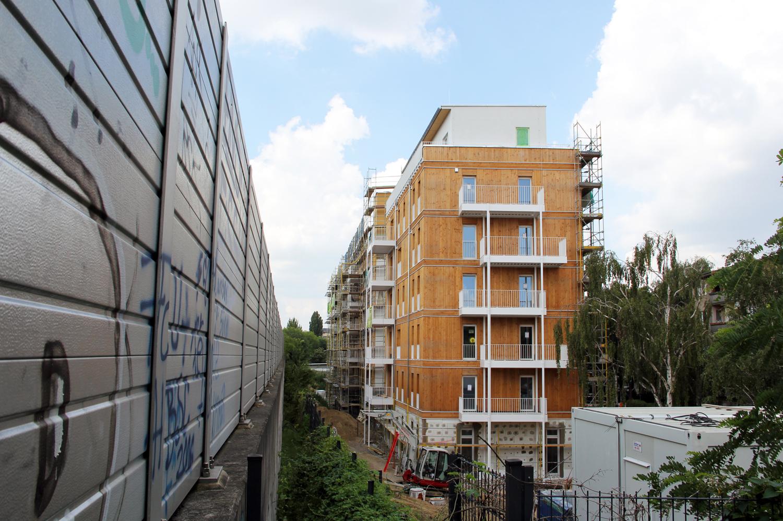 Das Holzhaus steht direkt an der Ringbahn, links ist die Schallschutzwand zu sehen. Foto: Hensel