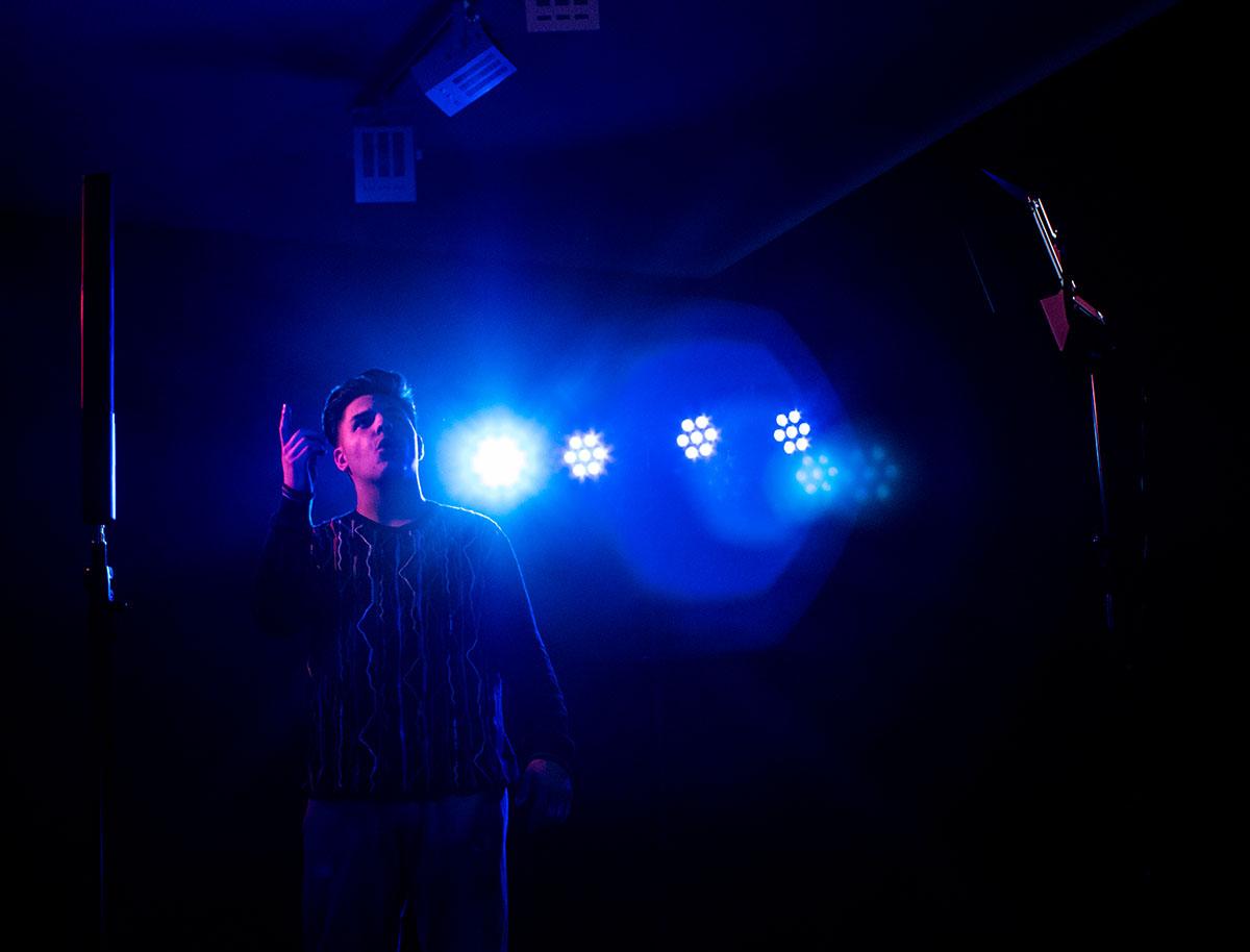 junger Mann singt im blau beleuchteten Studio
