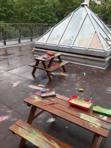 Eine Terrasse mit Tischen und Malzeug