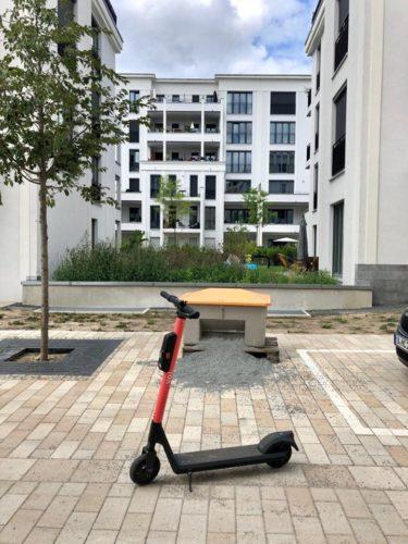 Ein elektrischer Tretroller steht vor einem Neubau