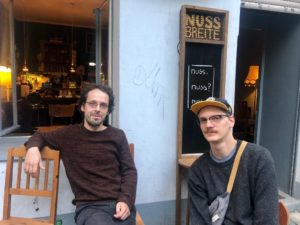 Zwei Männer sitzen vor ihrer Bar, der Nussbreite, die bald aufhört