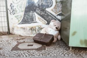 Ein Teddybär und ein alter Koffer in einer Straßenecke