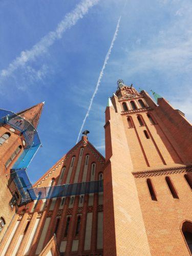 Blick an einem Kirchturm hoch in den blauen Himmel