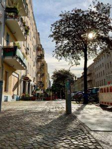 Die Spätsommersonne scheint auf den Bürgersteig einer Straße