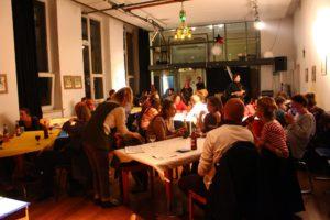 An einem großen Tisch sitzen viele Leute