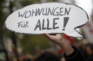 """Jemand hält ein Schild mit der Aufschrift """"Wohnungen für alle"""" hoch"""