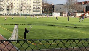 Zu sehen ist ein grünes Lacrossefeld, auf dem einzelne Spieler bei einem Spiel zu sehen sind.