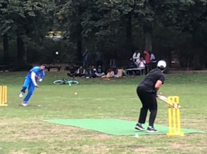 Zwei Spieler spielen Cricket. Der Spieler im Vordergrund hält einen Schläger, der hintere Spieler wirft einen Ball.