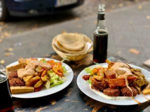 Zwei weiße Teller, jeweils mit Falafel, Halloumi und Salat. Im Hintergrund rundes arabisches Brot und eine Flasche Fritzcola.