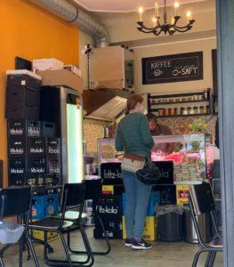 Innenraum des Dar4 Bistros. Zu sehen sind schwarze Stühle an beiden Seiten, Getränkekisten in der Mitte vor einer Theke. Davor steht eine Frau beim bestellen, Jeans und grünes Langarmshirt.