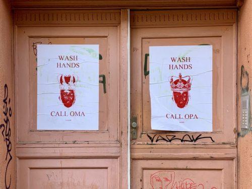 Zwei weiße Plakate auf einer rosa-orange farbigen Tür. Auf den Plakaten ist ein rotes Herz mit Krone zu sehen. Auf dem linken Plakat steht Wash Hands - Call Oma; auf dem rechten Plakat steht Wash Hands - Call Opa. Foto: Samuel Orsenne