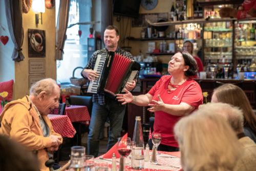 Ziehharmonikaspieler und Wirtin spielen Musik für die älteren Herrschaften. Ein Mann lacht freudig.