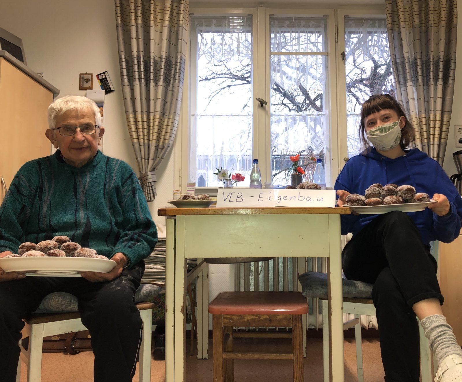 Am Küchentisch sitzt ein älterer Mann auf Abstand mit seiner Enkeltochter, welche zusammen traditionelle Pfannkuchen (Berliner) gebacken haben und diese in die Kamera zeigen